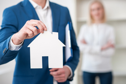 Close up of cheerful realtor selling an apartment. He is holding a placard in the shape of house. The woman is standing on background